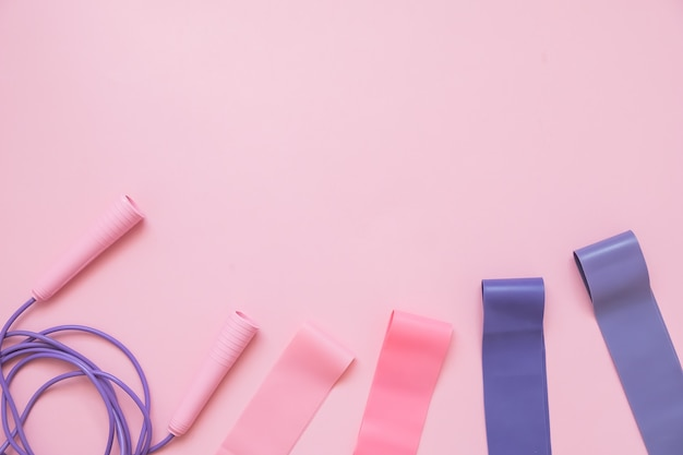 Pular ou pular corda e fitness elástico no fundo rosa. tendência de fitness.