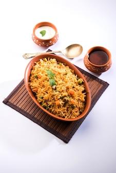 Pulav vegetal indiano ou biryani feito com arroz basmati, servido em tigela de terracota. foco seletivo