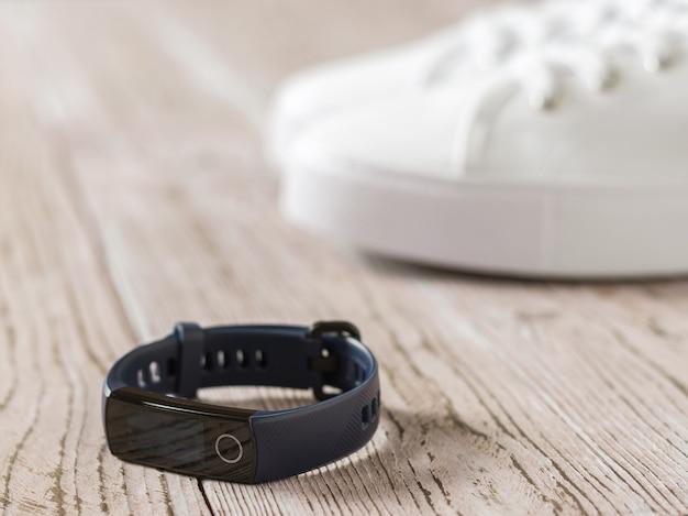 Pulseira azul inteligente no piso de madeira na superfície do tênis branco