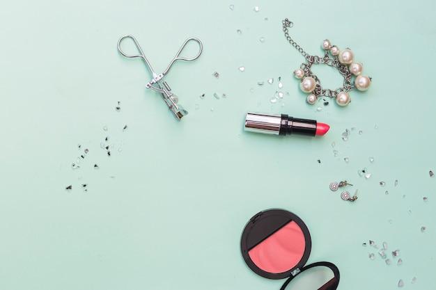 Pulseira; brincos de batom; rolos de blush e cílios em pano de fundo pastel