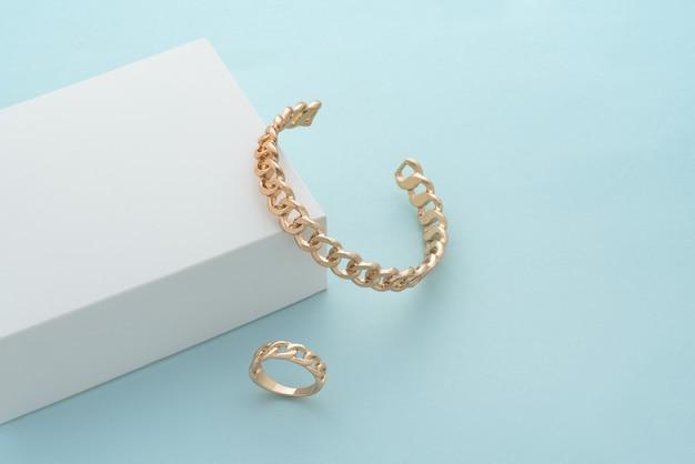 Pulseira de ouro em forma de corrente e anel em caixa branca em fundo azul com espaço de cópia