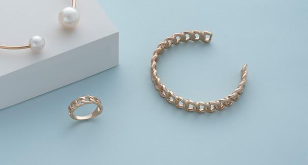 Pulseira de ouro em forma de corrente e anel em fundo azul com espaço de cópia