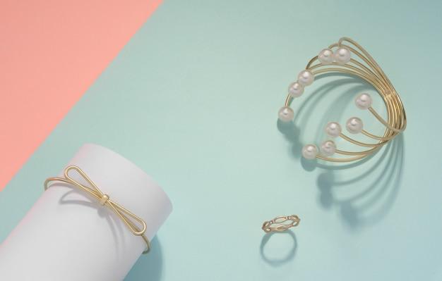 Pulseira de pérola dourada e anel de ouro sobre fundo de cor pastel, com espaço de cópia