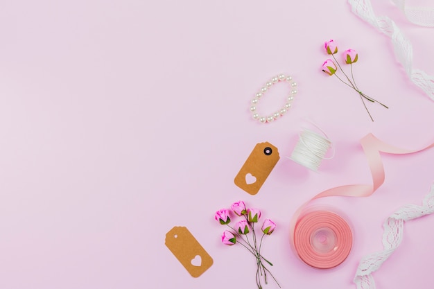 Pulseira de pérolas; tag; fita; carretel de linha; rendas e rosas artificiais no pano de fundo rosa