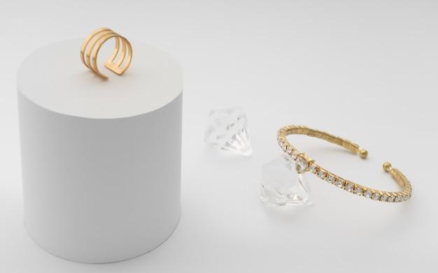 Pulseira e anel de diamante dourado na superfície branca