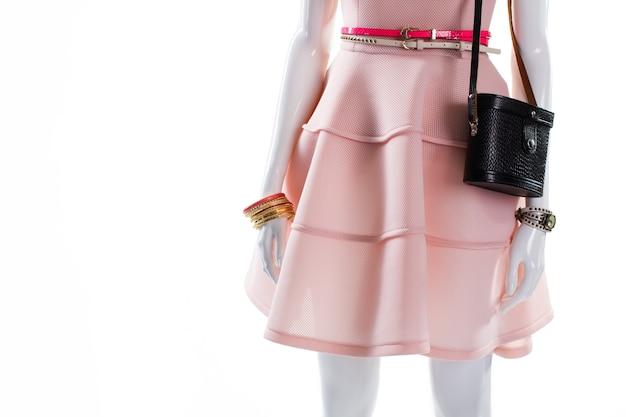 Pulseira e bolsa no manequim. manequim feminino com acessórios de moda. bolsa escura e pulseira dourada. cintos e pulseira brilhantes.