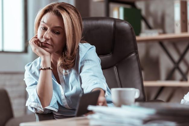 Pulseira elegante. mulher de negócios loira usando uma pulseira estilosa segurando um smartphone