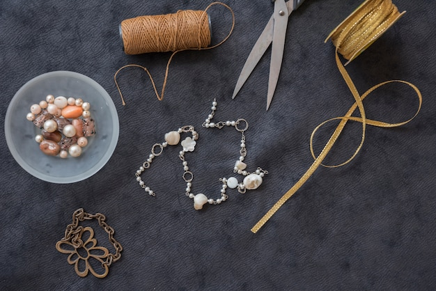 Pulseira feita com carretel de fios; miçangas; tesoura e fita dourada no pano de fundo texturizado preto