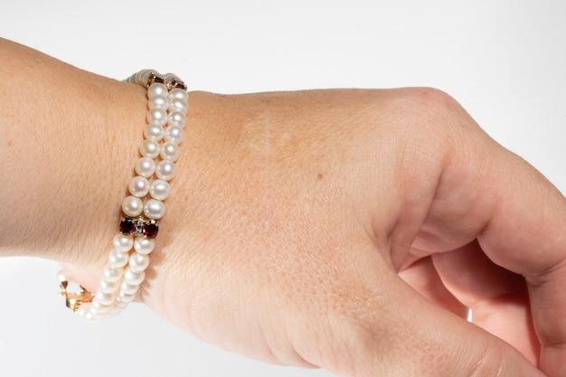 Pulseira feita de pérolas naturais e pedras preciosas na mão de uma mulher em um fundo branco