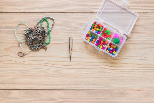 Pulseira; pinça e caixa de pérolas coloridas na mesa