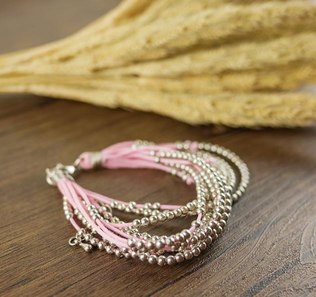 Pulseira rosa multi-strand na mesa de madeira