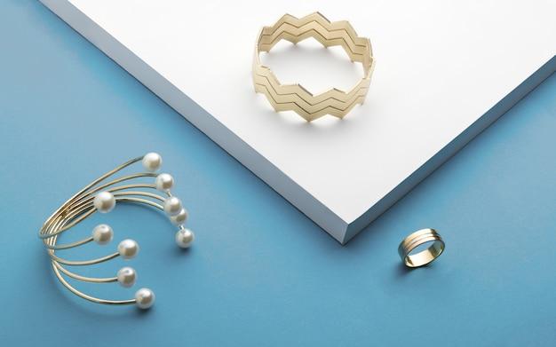 Pulseiras de ouro e anel de ouro sobre fundo branco e azul - pulseira de ziguezague e pérola dourada
