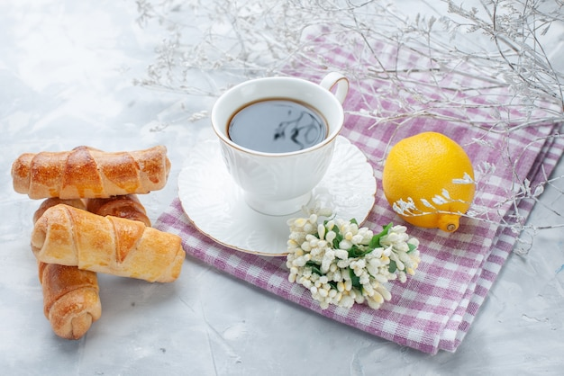 Pulseiras doces com recheio junto com café e limão em uma mesa leve