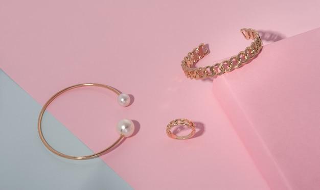 Pulseiras e anéis de joias douradas sobre fundo de papéis rosa e azul
