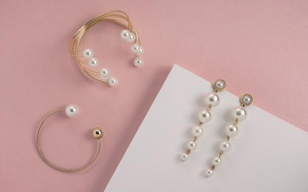 Pulseiras e brincos de pérola dourados na superfície branca e rosa