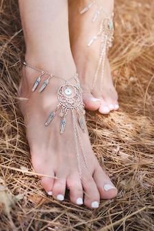 Pulseiras feitas à mão nas pernas de uma mulher, close-up, pedicure branca, estilo boho chic, conceito de cuidado corporal, sol ao ar livre