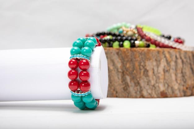 Pulseiras feitas de pérolas e pedras coloridas.