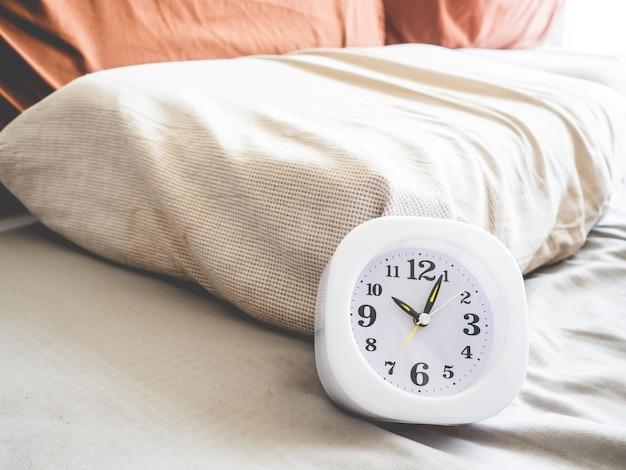 Pulso de disparo branco em 10 am na cama como o conceito da rotina do tempo e de vida.
