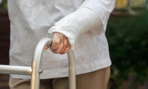 Pulso quebrado de mulher idosa usando andador no quintal