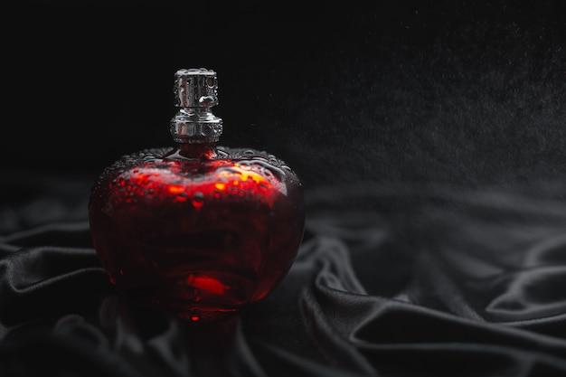 Pulverização de perfume em fundo escuro
