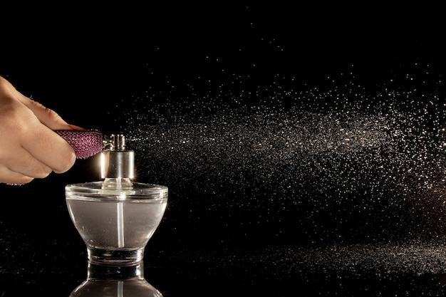 Pulverização de vidro de frasco de perfume em um fundo preto.