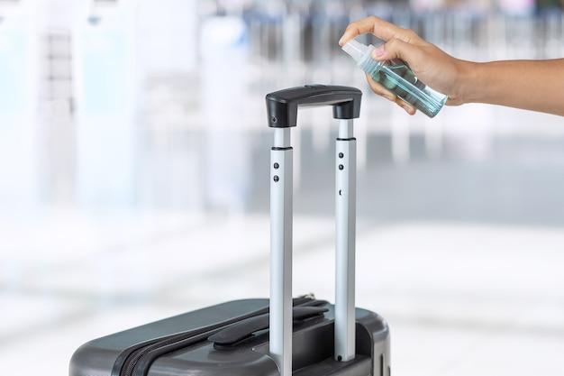 Pulverização manual de desinfetante de álcool na alça da bolsa de bagagem no aeroporto