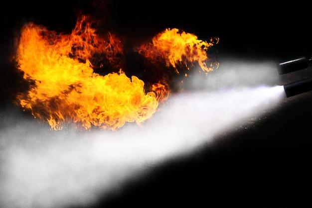 Pulverizador do extintor que luta a chama do calor no fundo preto.