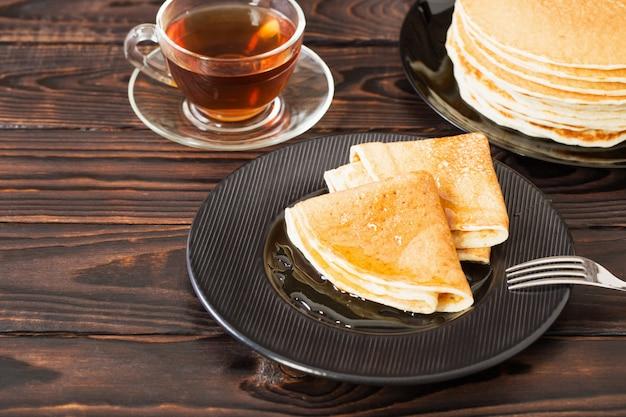 Puncakes com mel e xícara de chá em fundo de madeira velho