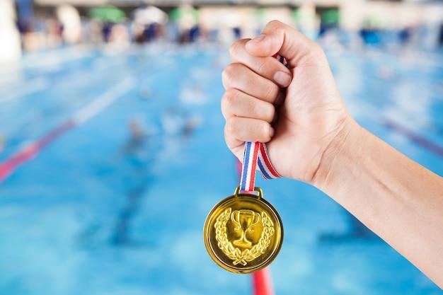 Punhado de homem asiático segurando medalha de ouro com fundo desfocado de piscina e competição de natação.