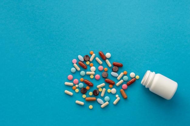 Punhado de pílulas coloridas derramadas fora da lata