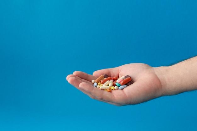Punhado de pílulas coloridas na palma da mão