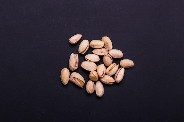 Punhado de pistaches em uma ardósia preta - lanche saudável.