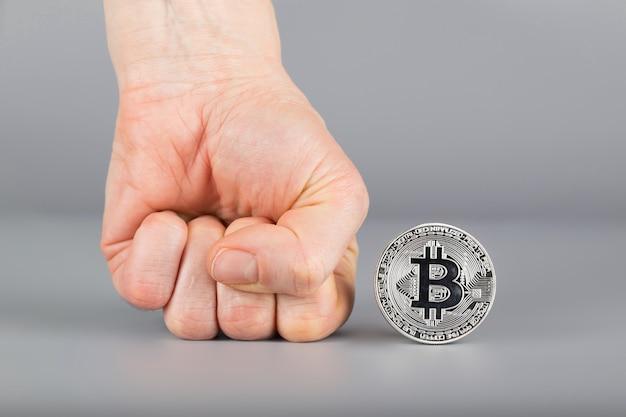 Punho humano e bitcoin. fechar-se