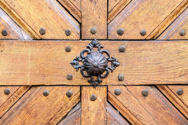 Punho oxidado velho da porta na porta de madeira.