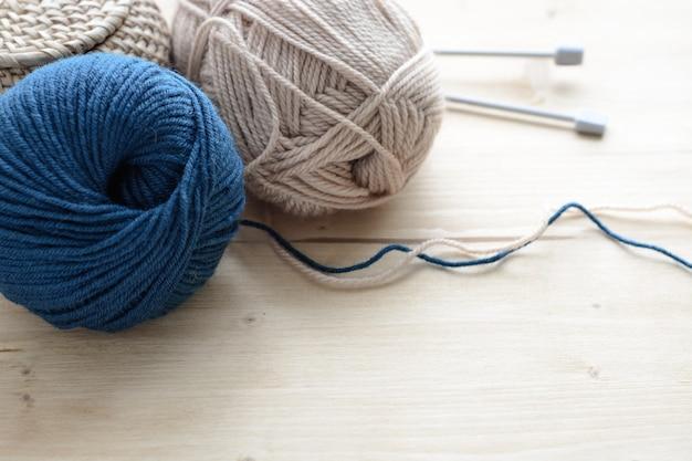 Punhos de fio de tricô azul e bege com agulhas na mesa de madeira
