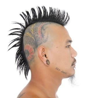 Punk asiático com cabelo estilo moicano, tatuagem na cabeça, orelha e piercing na boca isolado no branco