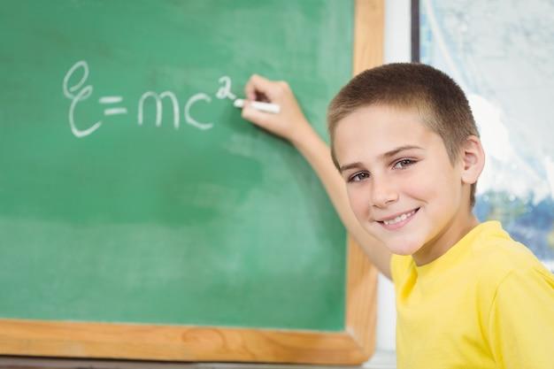 Pupila sorridente escrevendo no quadro-negro em uma sala de aula
