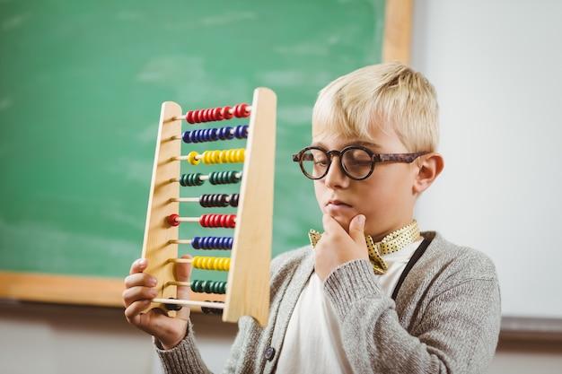 Pupila vestida como professora segurando ábaco