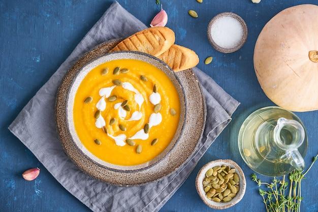 Pupmkin creme sopa purê na mesa de madeira azul brilhante escuro, almoço vegetariano dietético, vista superior