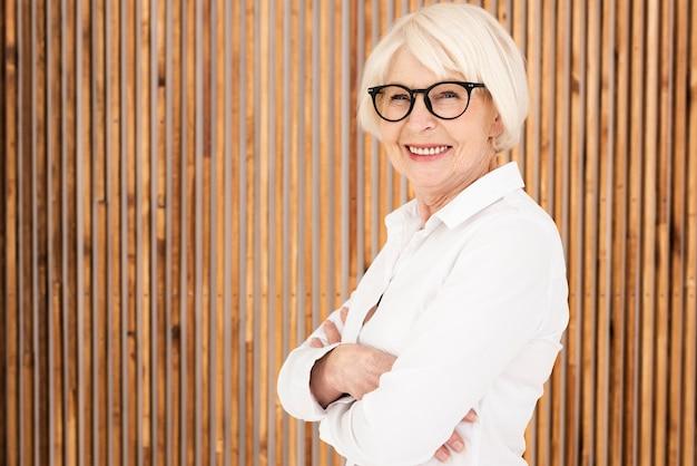Pura mulher velha com óculos de pé ao lado de uma parede de madeira