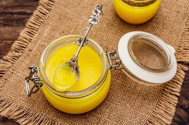 Pura ou desi ghee (ghi), manteiga derretida clarificada. conceito de dieta à prova de balas de gorduras saudáveis ou plano de estilo paleo. frasco de vidro, colher de prata de saco vintage.