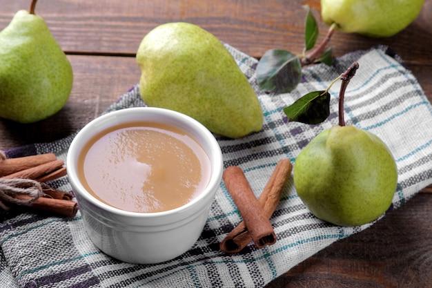 Purê com peras com peras frescas e canela no fundo em uma mesa de madeira marrom