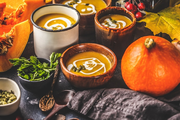 Puré de abóbora sopa de outono com creme em xícaras, a paisagem de outono