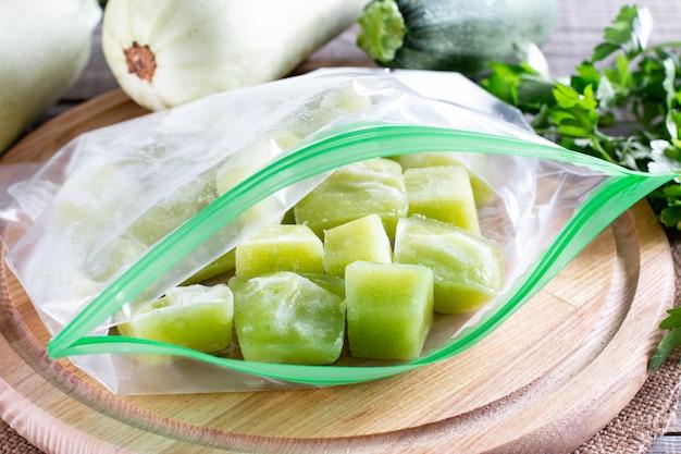 Purê de abobrinha congelada em um saco plástico na mesa de madeira. conceito de alimentos congelados