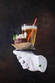 Purê de batata com carne e ao lado de um copo de cerveja. assenta numa luva branca. comida voadora