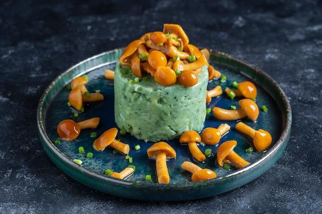 Purê de batata com espirulina verde e cogumelos com mel em um prato, close-up