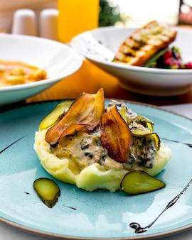 Purê de batatas com berinjela frita, picles e molho de natas em um prato