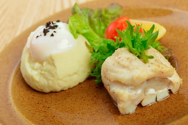 Purê de batatas com gema de ovo e fatia de peixe