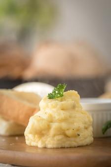 Purê de batatas em um prato sobre uma mesa de madeira