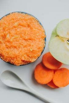 Purê de cenoura comida de bebê com maçãs verdes na tigela de cerâmica